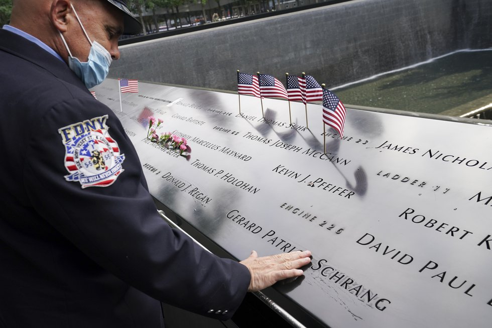 A mourner brushes water with his fingers over the name cut-outs of the deceased at the National...