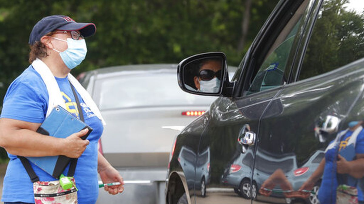 Wearing masks amid concerns of the spread of COVID-19, volunteer Carolina Salazar, left, talks with Maria Fernandez during a drive through food pantry distribution by Catholic Charities in Dallas, Thursday, July 2, 2020. (AP Photo/LM Otero)