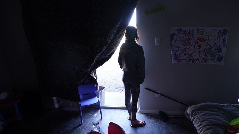 FILE - In this Feb. 23, 2021 file photo, Ricki Mills looks out from her home as she waits for a...