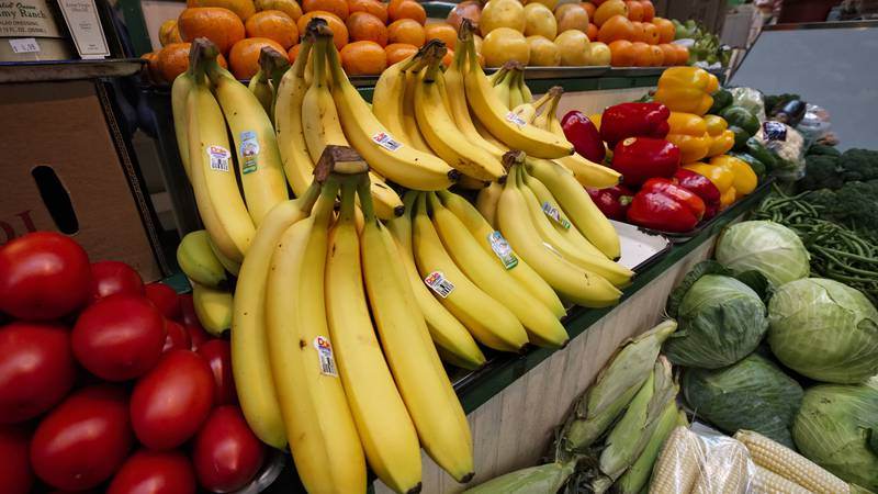 Bananas, tomatoes, peppers, corn, cabbage and citrus are displayed for sale at a market in...