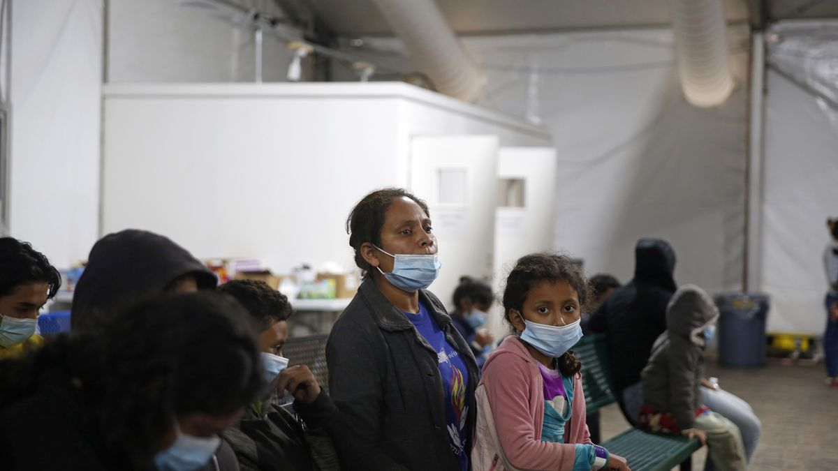 A migrant and her daughter wait for their turn at the intake area of the Donna Department of...
