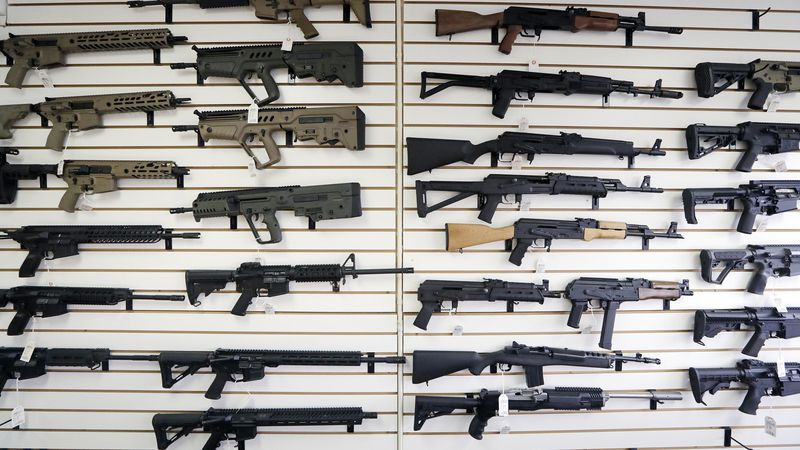 FILE - In this Oct. 2, 2018 file photo, semi-automatic rifles fill a wall at a gun shop in...